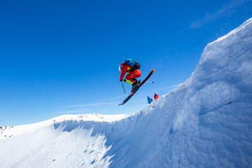 Fototapete - A skier is riding and jumping at mountain terrain.