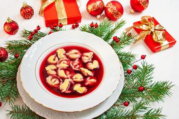 Obraz Tradycyjna polska potrawa wigilijna - czerwony barszcz z uszkami, w tle gałązki świerku, prezenty i czerwone bombki - fototapety do salonu