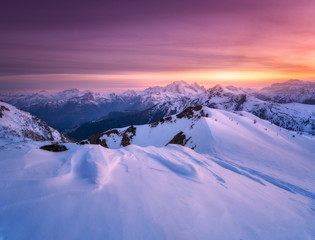Wall Mural - Colorful red sky with clouds and bright sunlight over the snow covered mountains at sunset in winter. Beautiful wintry landscape with snowy rocks and hills at dusk. Scenery with alps at frosty evening