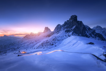 Wall Mural - Snowy mountains and blurred car headlights on the winding road at night in winter. Beautiful landscape with snow covered rocks, house, mountain roadway, blue starry sky at sunset in Dolomites, Italy