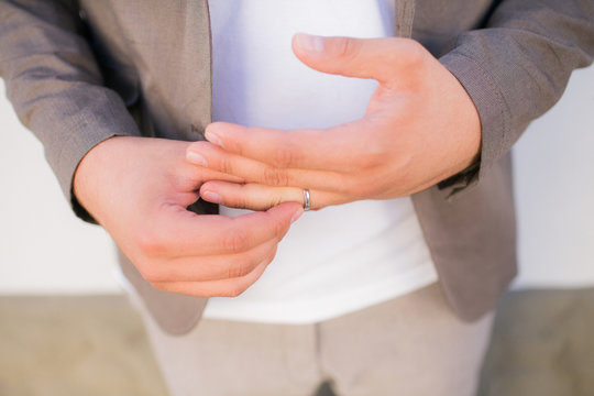 A man removes a wedding ring from a finger of his hand. Bad relationship with his wife. Divorce couples.