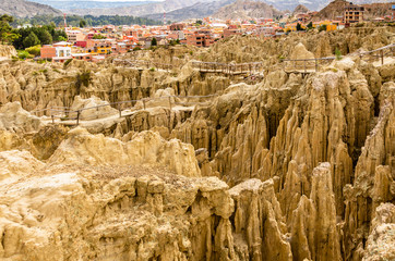 Maze of Moon Valley or Valle De La Luna  eroded sandstone spikes, with La Paz city suburb in the background, Bolivia