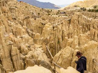Man walking in the maze of Moon Valley or Valle De La Luna among eroded sandstone spikes, near La Paz, Bolivia