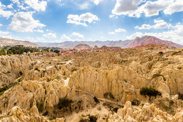 Maze of Moon Valley or Valle De La Luna  eroded sandstone spikes, with La Paz city suburb and mountains in the background, Bolivia
