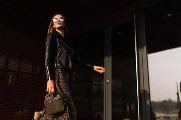 Street fashion. Beautiful young woman in sunglasses. glamorous, model gait. Urban fashion. Wall mural