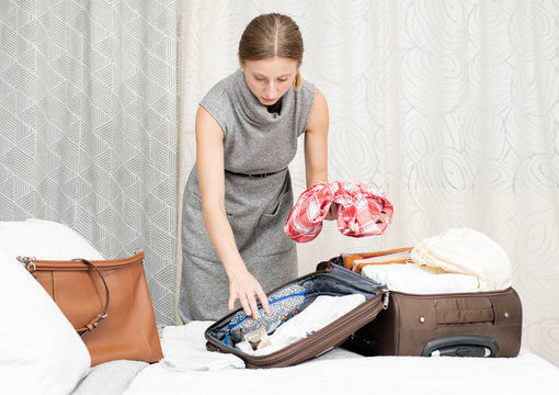 Beautiful woman packing suitcase in bedroom getting ready for road trip.