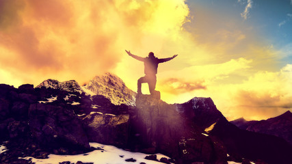 Man Praying Kneeling With Arms Open On Epic Mountain Top Summit With Light Shining With Arms Out On Top Of Mountain Peak