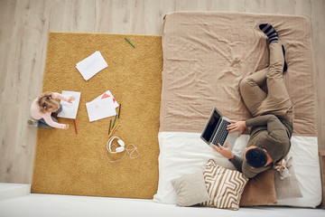 Above view background of little girl playing on floor in cozy bedroom interior with father using laptop, copy space