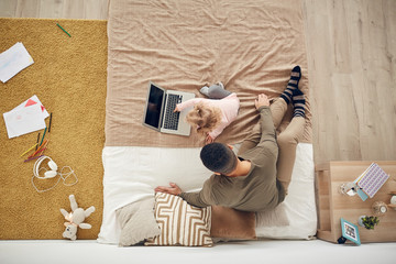 Above view background of little girl playing with father using laptop in cozy bedroom interior, copy space