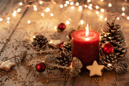 Christmas background - Red Advent candle with natural Xmas decoration, branches and pine cones on rustic wood