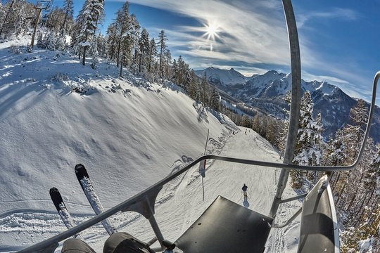 Skiing slope in the Alps with snowy trees in Les Arres, France from sitting on a ski lift