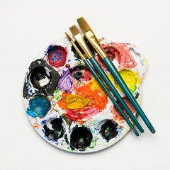 Colorful watercolor mixing plate with paintbrushes of different sizes on a blank, white background