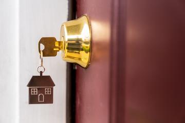 Metal silver house key in a door keyhole