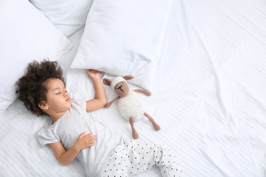 Little African-American girl with toy sleeping in bed