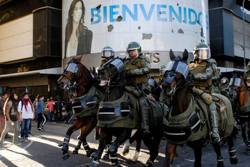 Riot policemen ride horses to disperse demonstrators during a protest against Chile's government in Concepcion