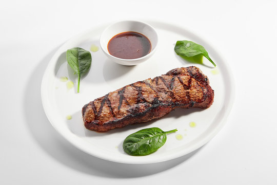 Striploin steak with sauce close up
