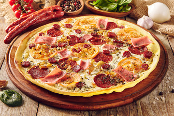 Meat and tomato pizza on wooden table close up