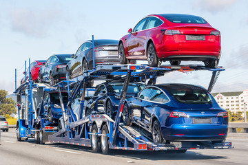 Aug 10, 2019 Burlingame / CA / USA - Car transporter carries Tesla Model 3 new vehicles on a freeway in San Francisco bay area, back view of the trailer;