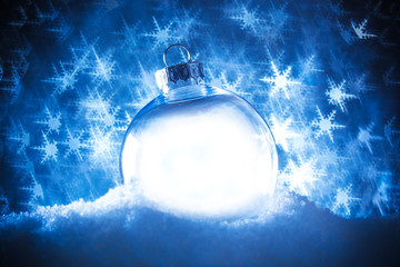 Clear Christmas ornament in snow surrounded by a bokeh of glittering lights in the shape of...