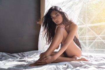 Sensual attractive woman posing over the window wearing sexy lingerie, looking at camera