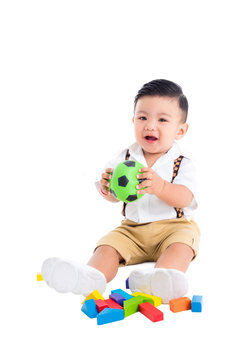 Little asian male toddler sitting on the floor and holding ball and smiles over white background