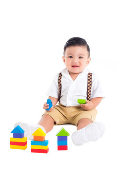 Little asian male toddler sitting on the floor and playing wood blocks over white background