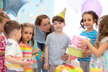 Preschool birthday child boy receiving gifts from his friends