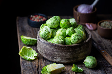 Fresh raw brussels sprout in bowl on wooden background