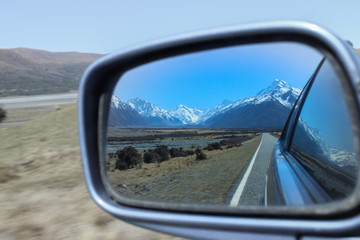 Looking in the side mirror of a car leaving the mountains behind.