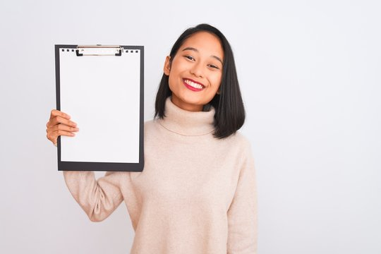 Young chinese inspector woman holding clipboard standing over isolated white background with a happy face standing and smiling with a confident smile showing teeth