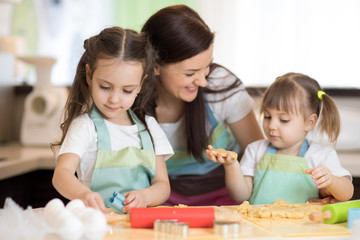 Happy family mother and kids preparing bakery together. Mom and children having fun cooking cookies in the kitchen. Homemade food and little helpers.