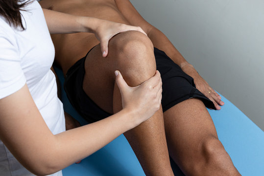 Therapist treating injured knee of athlete male patient - sport physical therapy concept.