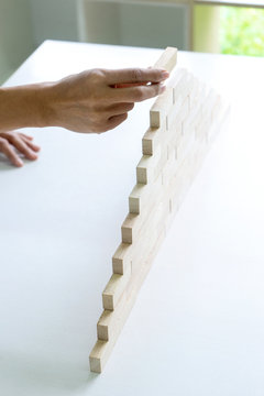 Young businessman try to build wall and tower from wooden