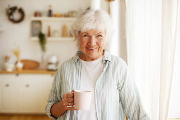 People, lifestyle, age and retirement. Waist up image of cheerful happy European female pensioner relaxing at home, having herbal tea, smiling broadly at camera, posing against kitchen background