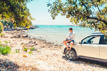 man with coffee cup standing near car at sea summer beach