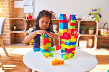 Beautiful toddler girl playing with construction blocks at kindergarten