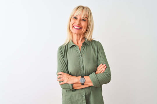 Middle age woman wearing green casual shirt standing over isolated white background happy face smiling with crossed arms looking at the camera. Positive person.