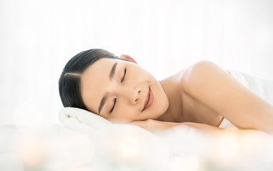 Closeup beautiful asian young woman lying down on massage bed at Asian luxury spa wellness centre or hotel. Portrait of beauty woman relaxing with copy space, healthcare lifestyle concept banner.