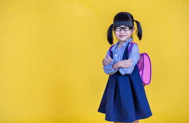 Portrait of young happy little cute asian girl in school uniform isolated on yellow background with copy space. Education for toddler or preschool, childhood lifestyle back to school concept
