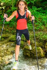 Frau quert beim Trail Running einen kleinen Bach