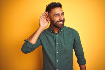 Young indian businessman wearing elegant shirt standing over isolated white background smiling with hand over ear listening an hearing to rumor or gossip. Deafness concept.