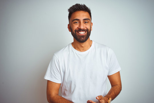 Young indian man wearing t-shirt standing over isolated white background with hands together and crossed fingers smiling relaxed and cheerful. Success and optimistic