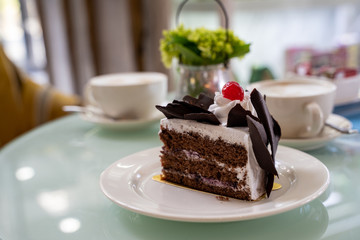 Delicious three layer chocolate cake with shavings and a cherry on a plate at a cafe