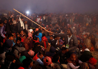 "A volunteer controls a crowd using a stick during the ritual before the sacrificial ceremony of the ""Gadhimai Mela"" festival at Bariyarpur"