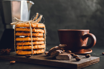 Homemade cookies and brown cup with coffee on dark background