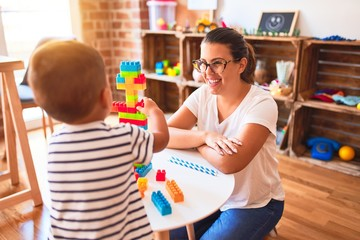 Beautiful teacher and toddler boy playing with construction blocks bulding tower at kindergarten
