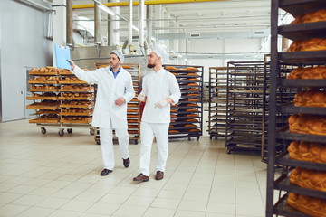 The technologist and baker speak in a bread factory.