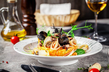 Italian food concept. Risotto with seafood, mussels, octopuses, squid. Serving dishes in a white...
