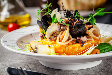 Italian food concept. Risotto with seafood, mussels, octopuses, squid. Serving dishes in a white plate. Modern serving in a restaurant. Background image. Copy space. Fototapete