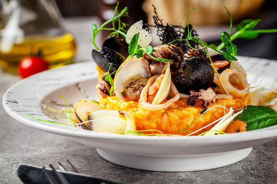 Italian food concept. Risotto with seafood, mussels, octopuses, squid. Serving dishes in a white plate. Modern serving in a restaurant. Background image. Copy space.